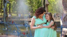 A mulher gravida e sua filha pequena estão estando perto da fonte nos vestidos filme