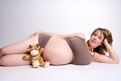 Mulher gravida em seu lado com um brinquedo Fotos de Stock Royalty Free