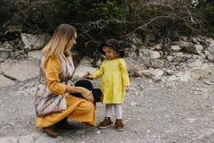 Mulher gravida em um vestido amarelo que mantém a mão sua menina exterior fotos de stock