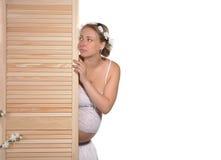 A mulher gravida espreita para fora atrás da tela fotografia de stock royalty free