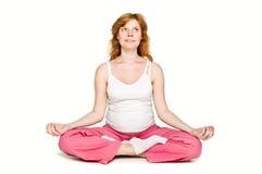 A mulher gravida está em uns lótus da posição imagem de stock