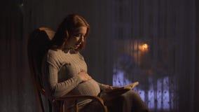 A mulher gravida está sentando-se na cadeira de balanço na sala escura A senhora lê o livro alto ao bebê por nascer vídeos de arquivo