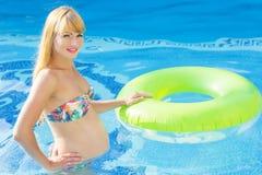 A mulher gravida está nadando com anel de borracha verde Imagem de Stock