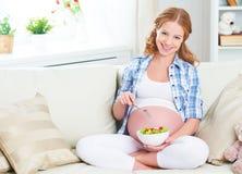 A mulher gravida feliz come a salada saudável do vegetal do alimento Imagens de Stock
