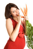 mulher gravida feliz de 21 semanas com cenouras frescas Imagens de Stock Royalty Free