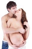 Mulher gravida feliz do abraço do homem Imagens de Stock