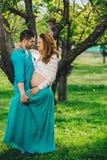 Mulher gravida feliz e seu marido na madeira no por do sol da mola imagem de stock
