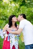 Mulher gravida feliz e seu marido no parque Foto de Stock Royalty Free