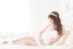 Mulher gravida feliz em um interior da luz fotografia de stock