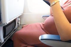 A mulher gravida feliz está viajando ao destino pelo sittin plano imagens de stock