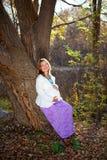 Mulher gravida feliz na natureza da queda imagens de stock