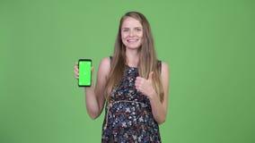 Mulher gravida feliz nova que mostra o telefone e que dá os polegares acima vídeos de arquivo