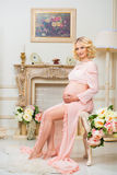 Mulher gravida feliz nova que senta-se no sofá no vestido de molho branco do laço imagens de stock