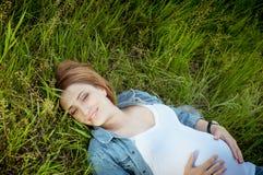 Mulher gravida feliz que encontra-se na grama Fotos de Stock Royalty Free