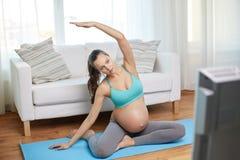 Mulher gravida feliz que exercita em casa Imagens de Stock Royalty Free