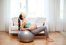 Mulher gravida feliz que exercita no fitball em casa Fotografia de Stock Royalty Free