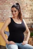 Mulher gravida feliz que senta-se em casa fotos de stock