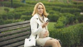 Mulher gravida feliz que senta-se no banco de parque com o smartphone, afagando a barriga video estoque
