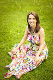 Mulher gravida feliz que senta-se no gramado Imagem de Stock Royalty Free