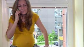 Mulher gravida irritada louca que mostra emoções negativas ao falar no smartphone vídeos de arquivo