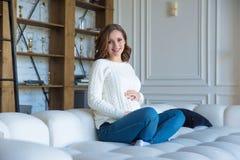 Mulher gravida na camiseta e na calças de ganga brancas em casa na cama foto de stock royalty free