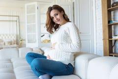 Mulher gravida na camiseta e na calças de ganga brancas em casa na cama imagens de stock