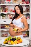 Mulher gravida na cozinha com uma placa da salada de fruto Imagem de Stock