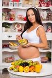 Mulher gravida na cozinha que come a salada de fruto Dieta saudável e vitaminas durante últimos meses da gravidez Foto de Stock Royalty Free