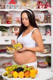 Mulher gravida na cozinha que come a salada de fruto Dieta saudável e vitaminas durante últimos meses da gravidez Fotos de Stock Royalty Free