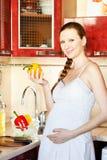 Mulher gravida na cozinha que faz uma salada Fotografia de Stock Royalty Free