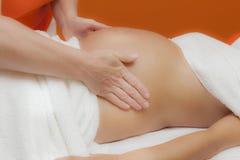 Mulher gravida na massagem pré-natal, efeito da claridade do encanto fotografia de stock