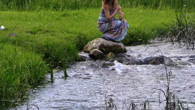 A mulher gravida na pedra e deixou o navio de papel do origâmi flutuar a água video estoque