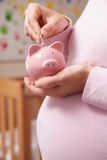 Mulher gravida no berçário que põe o dinheiro no mealheiro Fotografia de Stock Royalty Free