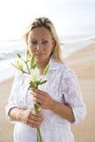 Mulher gravida no branco na flor da terra arrendada da praia imagens de stock