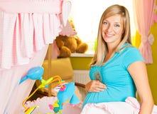 Mulher gravida no quarto do bebê imagens de stock