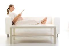 Mulher gravida no sofá fotos de stock royalty free