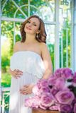 Mulher gravida, no vestido branco no gramado da natureza com o miradouro com flores fotografia de stock