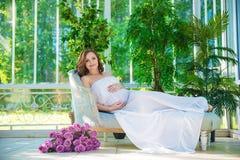 Mulher gravida, no vestido branco no gramado da natureza com o miradouro com flores foto de stock royalty free