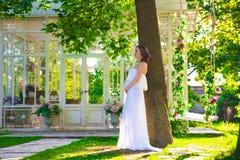 Mulher gravida no vestido branco no gramado da natureza com o miradouro com flores imagens de stock