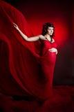 Mulher gravida no vestido de ondulação vermelho do vôo. Imagem de Stock Royalty Free