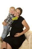 A mulher gravida no vestido preto abraçou pelo menino novo fotografia de stock royalty free