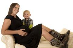Mulher gravida no vestido preto e botas que sentam-se pelo menino novo fotos de stock