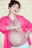 A mulher gravida nova bonita olha o pulso de disparo e o childb de espera Fotos de Stock