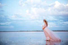 Mulher gravida nova bonita que aprecia o sol no lago cor-de-rosa imagem de stock