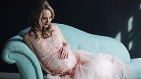 Mulher gravida nova bonita que senta-se em um sofá que olha na câmera e nas posses suas mãos em seu estômago lento vídeos de arquivo