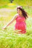 Mulher gravida nova com cabelo encaracolado longo no verão Fotografia de Stock