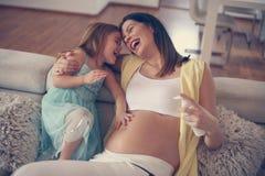 Mulher gravida nova com filha Imagem de Stock