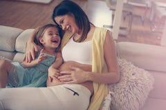 Mulher gravida nova com filha em casa Foto de Stock