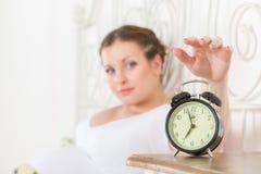 A mulher gravida nova dorme na cama no quarto. imagens de stock royalty free