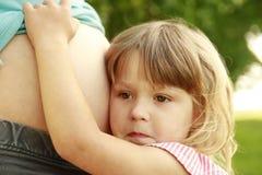 Mulher gravida nova e sua filha pequena na natureza Imagens de Stock